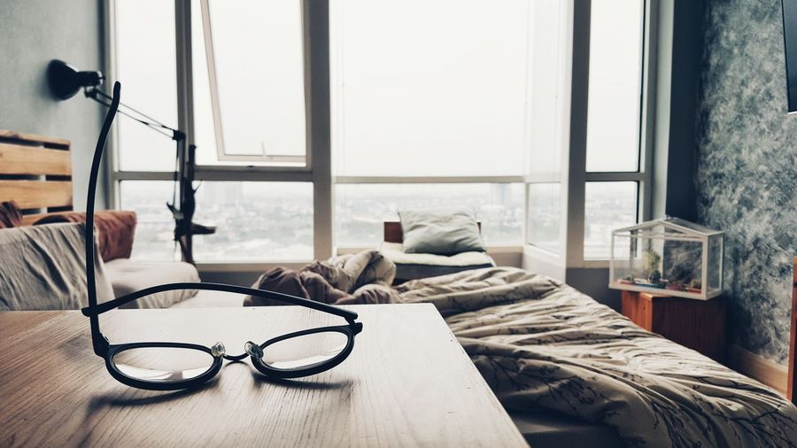 Eyeglasses  on Table in Bedroom of an Apartment . Window Indoors  Luxury Day Architecture Life Domestic Interior Room Bed Home Chair Calm Peaceful Quiet Chill View Relax