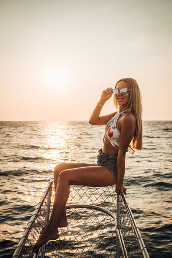 Fashionable young woman sitting on fence by sea against clear sky during sunset