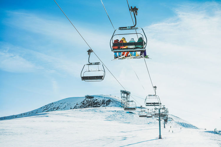 People Sitting On Overhead Cable Car Over Snowcapped Mountains Against Sky
