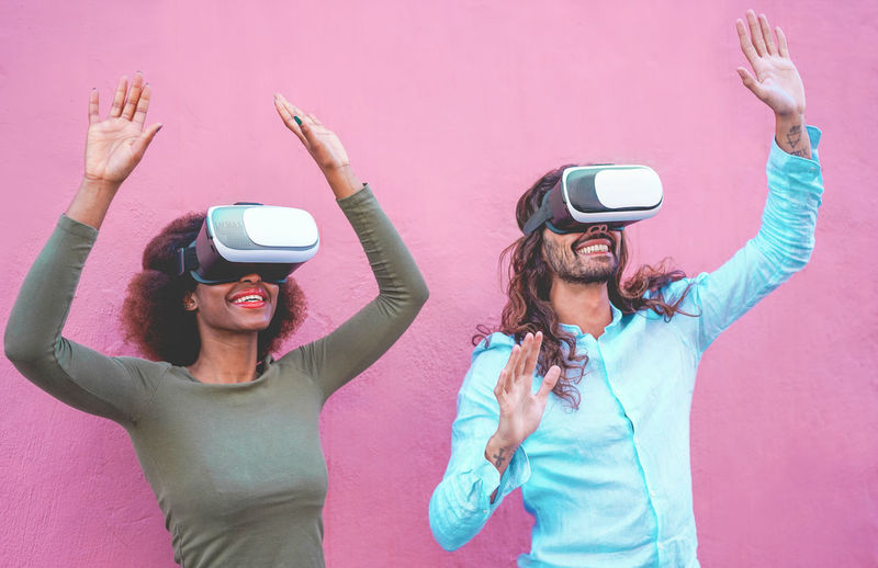 Couple gesturing while wearing virtual reality simulator against wall