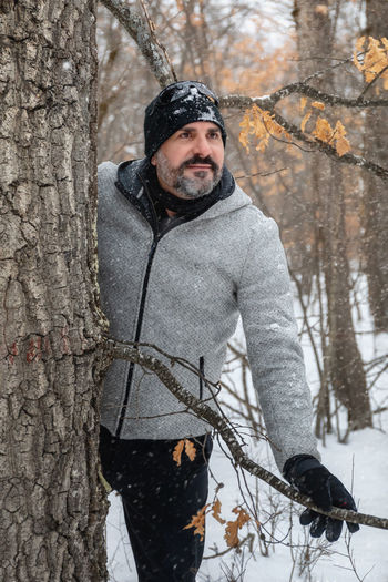 Portrait of man standing by tree trunk during winter