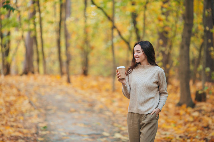 Woman standing in forest during autumn