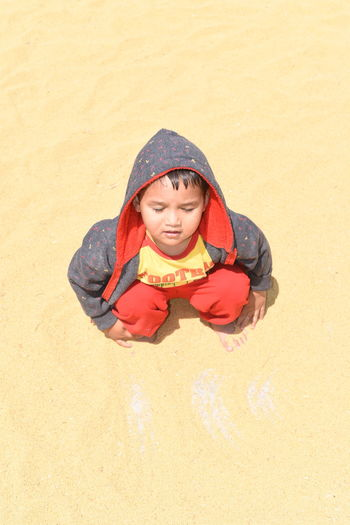 High angle view of boy crouching on sand at beach