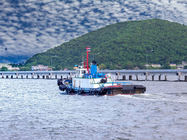 Tug boat is sailing to berth after completed assist vessel to alongside. Assist Barge Beauty In Nature Boat Day Mode Of Transport Moored Mooring Mountain Nature Nautical Vessel Ocean Oil Field Outdoors Pull Push Sailing Sea Sky Supply Towing Transportation Tug Vessel Water