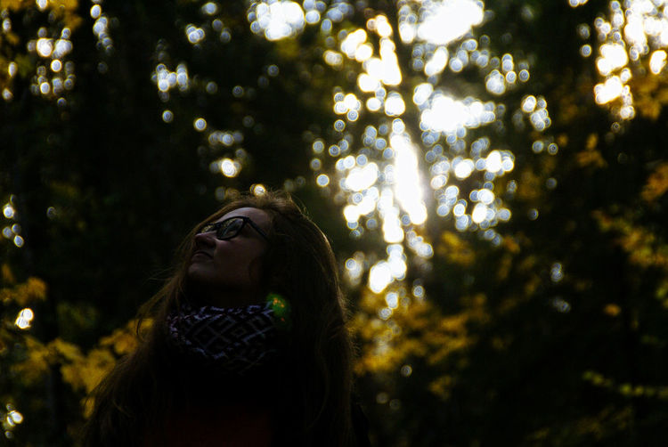 Low angle view of young woman standing against trees