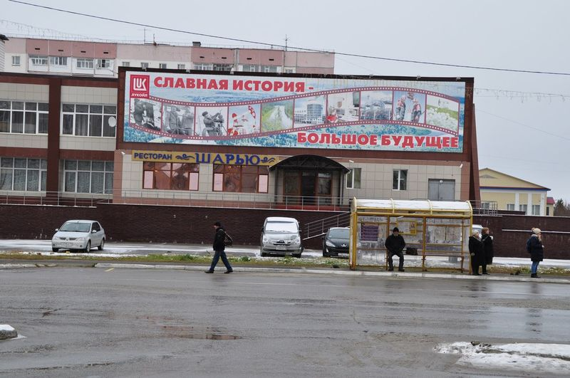 "Citizens waiting for the bus in Usinsk, northern sign is an ad for oil giant Lukoil and reads: ""glorious history - mighty future"" Usinsk Russia Building Exterior Architecture Built Structure City Real People Street Text Group Of People Transportation Communication Sign"
