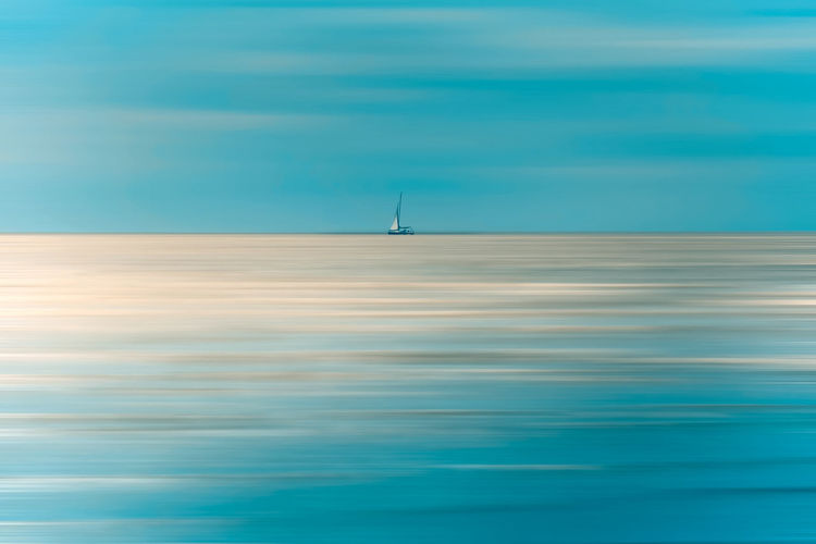 lonely sailboat on the ocean Lonely Air Vehicle Airplane Beauty In Nature Blue Cloud - Sky Day Flying Horizon Over Water Industrial Windmill Nature No People Ocean Outdoors Sailboat Sailboats Scenics Sea Sky Transportation Water Waterfront Wind Power Wind Turbine Windmill