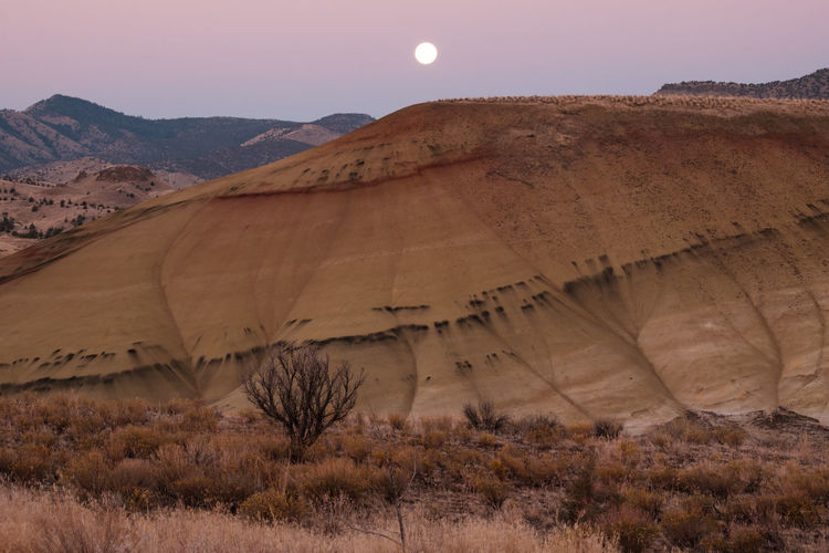 Early morning. Sunset and moon at Painted Hills, John Day Fossil Beds near Mitchell, Oregon Desert Nature Landscape Geology Painted Hills John Day Fossil Beds Historical Destination National Park Oregon Mountain Sky Sunrise Moon Sunburst Outdoors Pacific Northwest  Hiking Roadtrip Fossil Rocks Geological Formation Morning Paleontology Scenic Byway