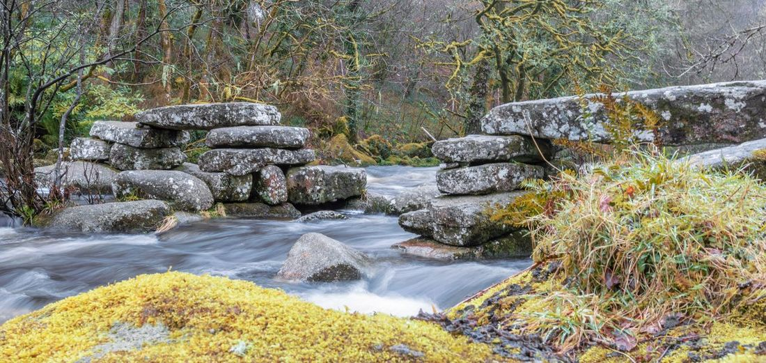 Medieval clapper bridge over river Dart Dartmeet Dartmoor History River Crossing Stone Granite Bridge Medieval Clapper Bridge Water Nature Rock - Object Motion Outdoors No People Beauty In Nature Day Tree Scenics Forest Waterfall
