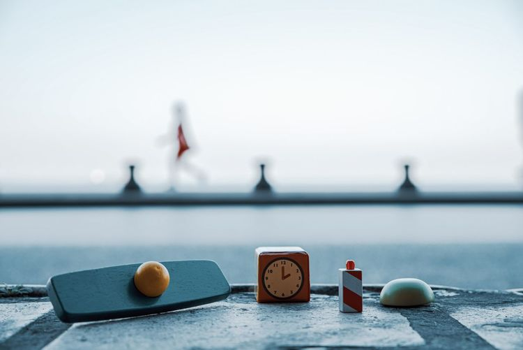 Close-up of clock on table against sea