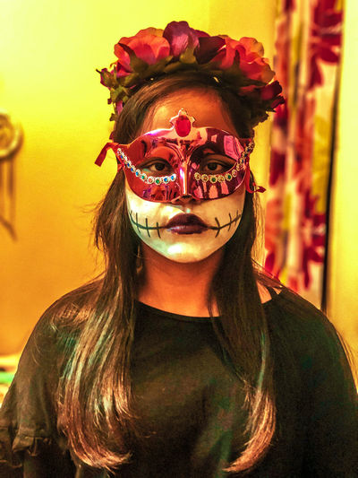 Portrait of teenage girl wearing mask at home