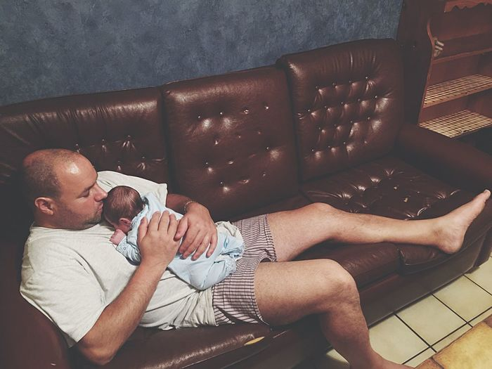 High angle view of father holding newborn baby while reclining on sofa at home