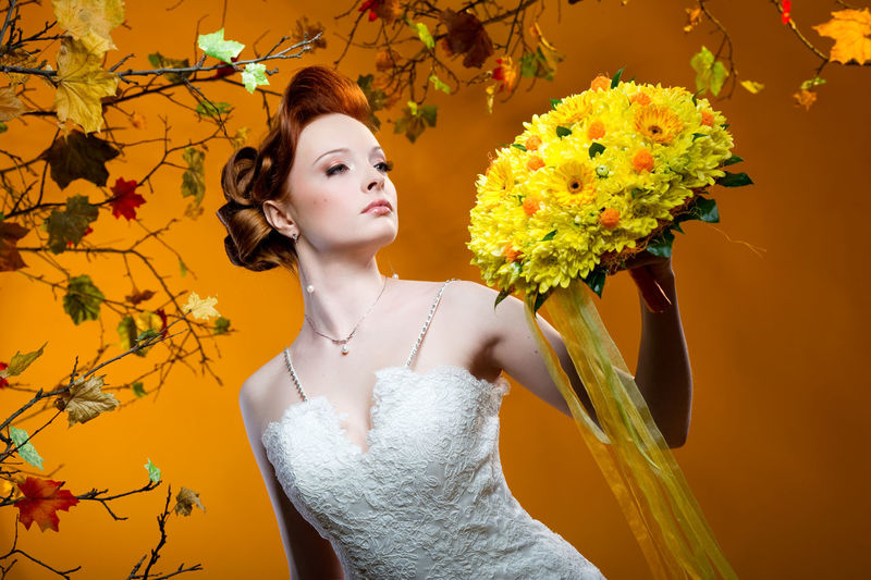 Beautiful Bride Looking At Bouquet While Standing Against Orange Background