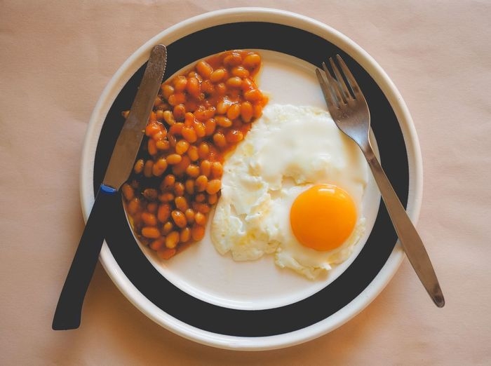 Close-up of baked beans with fried egg