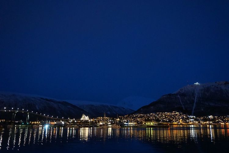 """""""Beauty of the twinkling lights warms the coldest nights"""" - Janisa City Lights At Night Urban Landscape Night Scene Night Photography Warm Lights Twinkling Lights Reflections In The Water Snow Capped Mountains Majestic Beauty In Nature Water Water Front  Illuminated Reflection Night Lake Tranquil Scene Tranquillity Travel Destinations Travel Photography EyeEm Nightscape - Traveling in Tromsø , Norway"""