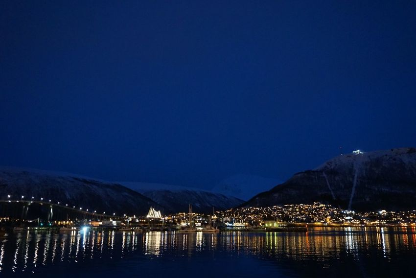 """Beauty of the twinkling lights warms the coldest nights"" - Janisa City Lights At Night Urban Landscape Night Scene Night Photography Warm Lights Twinkling Lights Reflections In The Water Snow Capped Mountains Majestic Beauty In Nature Water Water Front  Illuminated Reflection Night Lake Tranquil Scene Tranquillity Travel Destinations Travel Photography EyeEm Nightscape - Traveling in Tromsø , Norway"