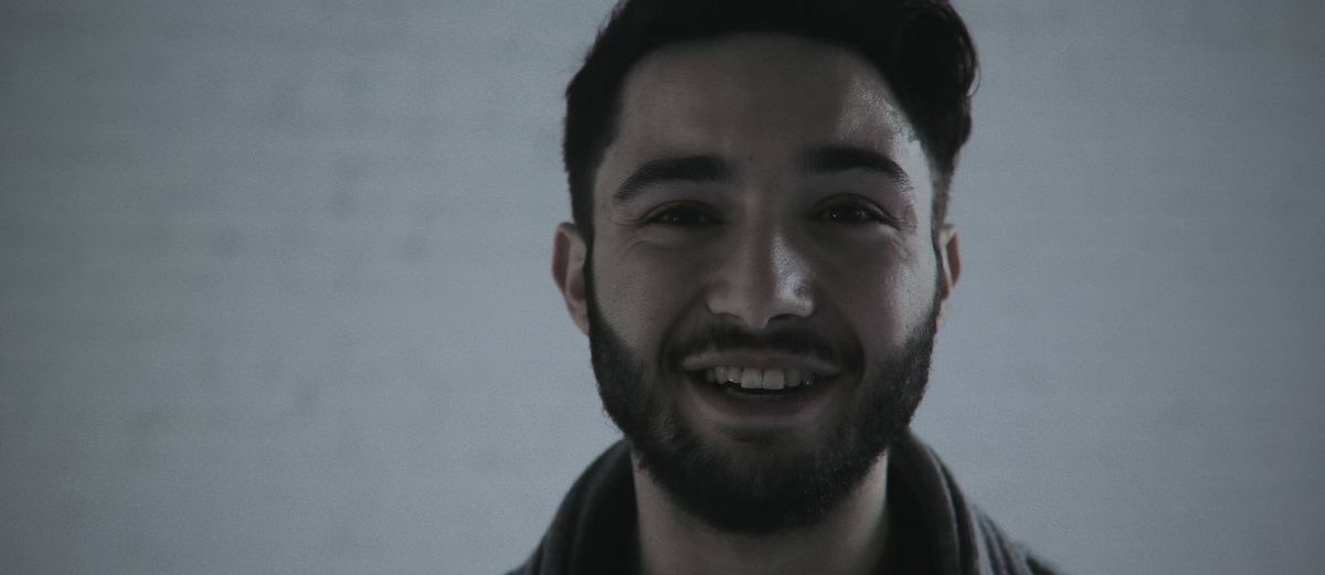 Close-up portrait of happy bearded man against wall