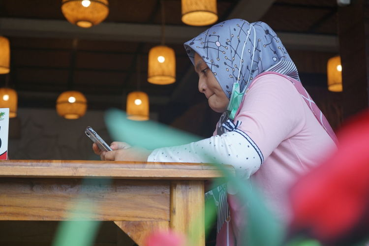 A woman is sitting in a restaurant looking at a cell phone