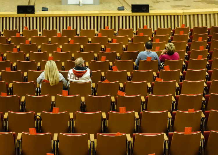 Rear view of people sitting on chairs in auditorium