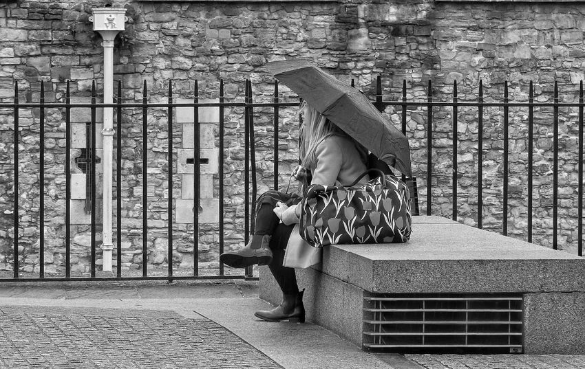 Full Length One Person Real People Street Photography Black And White Monochrome Umbrella Outdoors Day Shelter lifestyles Adults Only London Sitting Outside Seated People Watching Sheltering From The Rain Sheltering Young Adult Rainy Day Railings Drainpipe Bench Crossed Legs Wall Pavement
