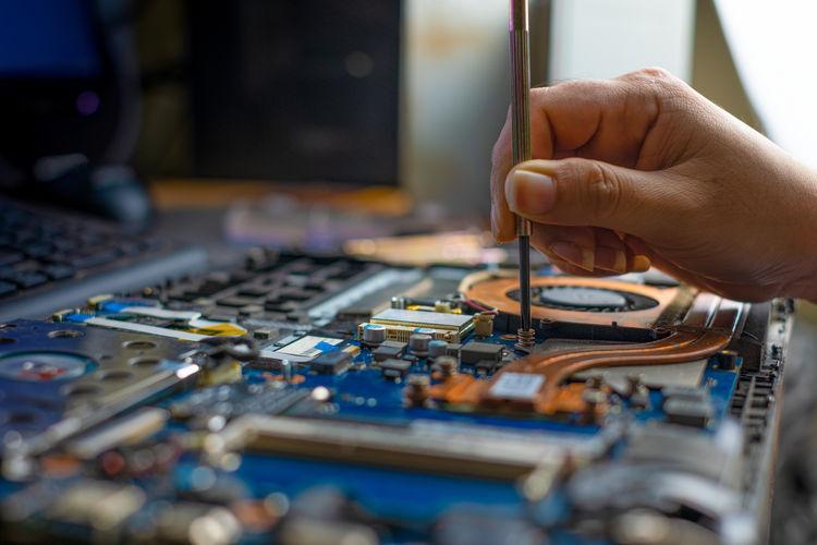 Cropped hand repairing motherboard