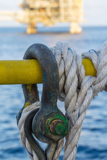 shackle and rope on handrail Rigging Platform Close-up Shackle Rope Handrail  Yellow Thread Pin Bolt Secured Secure Tie Offshore Offshore Life Ocean Nautical Maritime Oil And Gas Industry