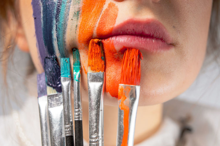 Close-up of young woman painting face and lips