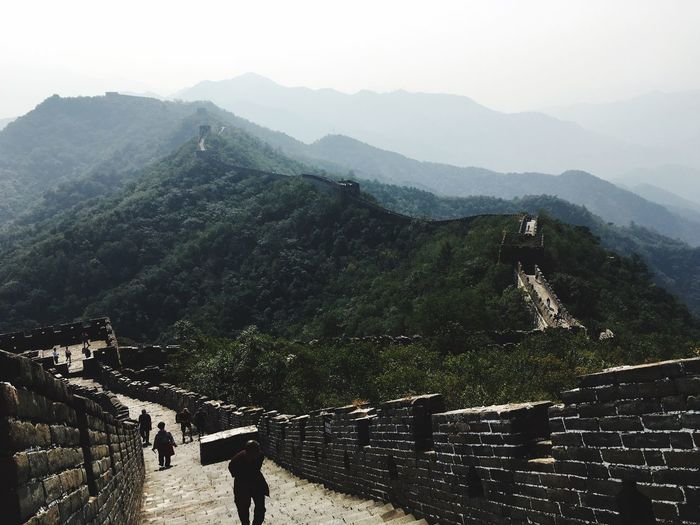 People Walking On Great Wall Of China Against Mountains