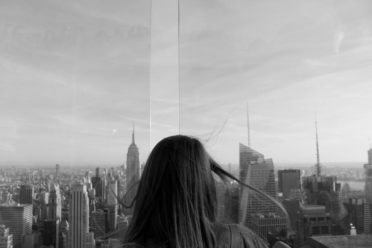 Rear view of woman looking at modern buildings in city against sky