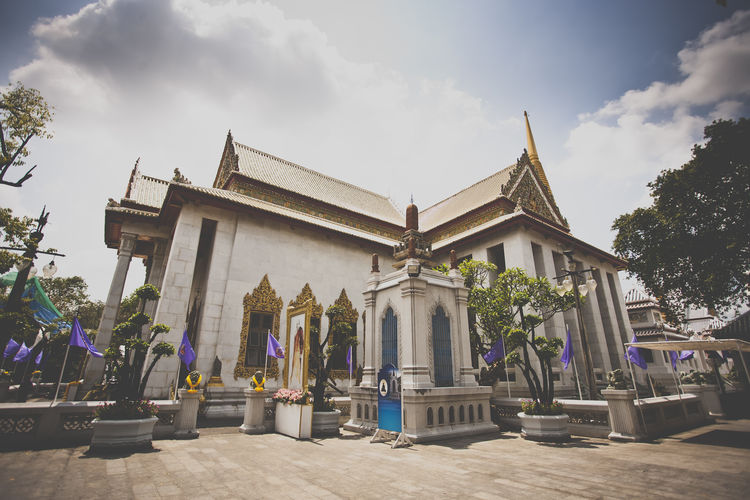 a temple in Thailand Architectural Column Architectural Feature Architecture Building Exterior Built Structure Church Cloud Cloud - Sky Day Famous Place History Human Representation In Front Of Low Angle View Outdoors Place Of Worship Religion Sculpture Sky Spirituality Statue Temple - Building The Past Tourism
