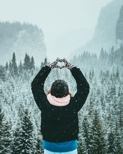 Rear View Of Man Making Heart Shape During Snow Fall