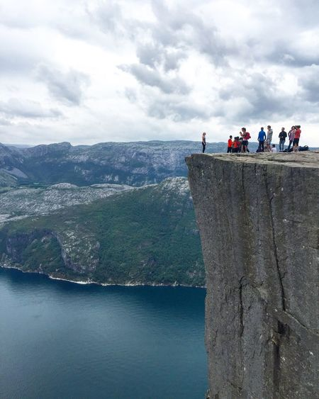 Tourists standing on cliff by sea against cloudy sky