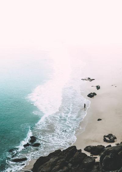 Aerial view of rocks in sea against sky