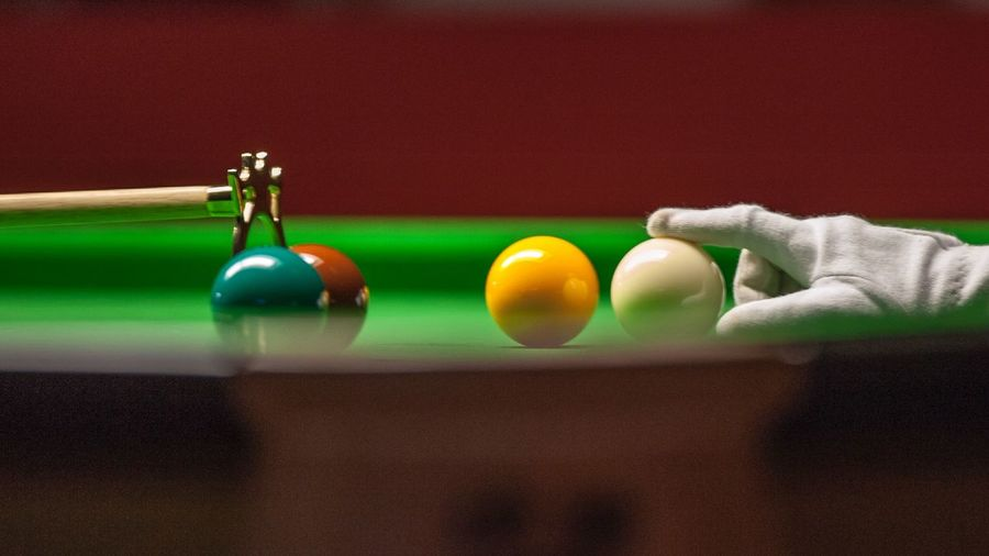 Close-up of hand adjusting ball on pool table