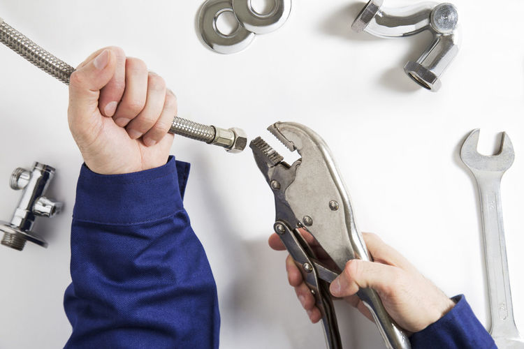 Cropped Hands Of Man Holding Hand Tools On White Table