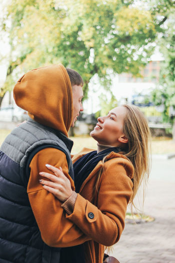 Couple embracing on footpath in city