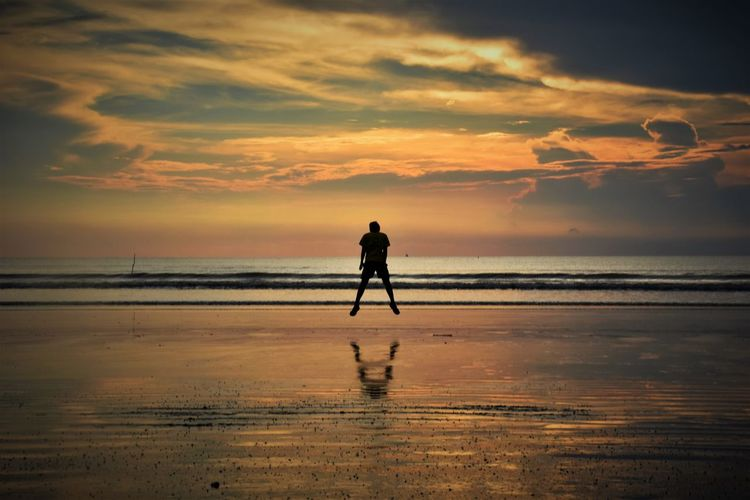 Silhouette Man Jumping Against Sea During Sunset