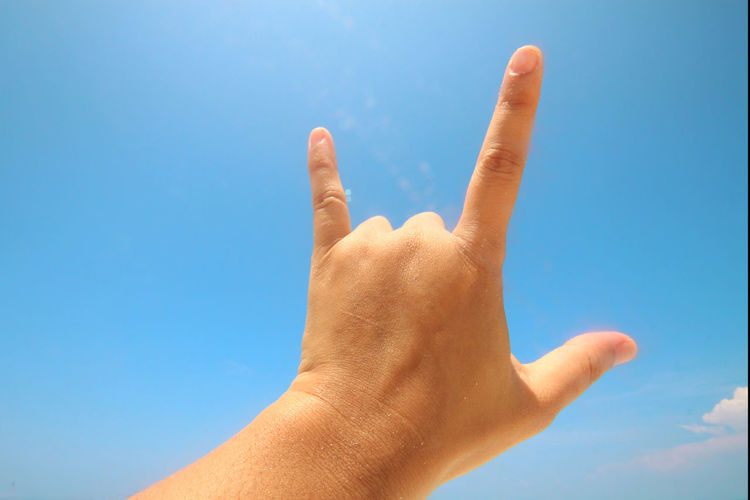 Low angle view of hand gesturing against sky