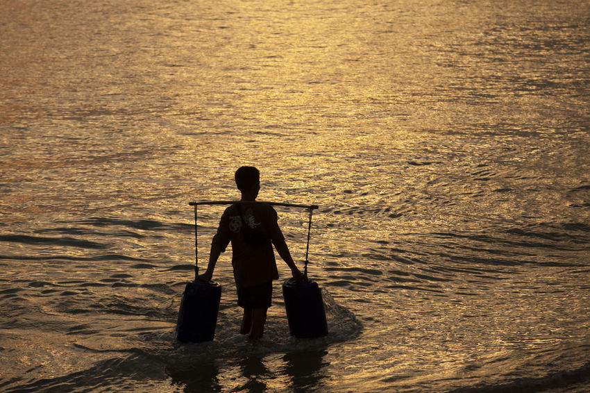Silhouette of Man Taking Water in Bali Bali Cultures Fisherman Full Length Kedonganan Nature Occupation One Person Outdoors People Rear View Sea Silhouette Standing Water Working