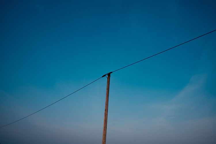 Sky Electricity  Blue Low Angle View Cable No People Nature Power Line  Connection Fuel And Power Generation Day Power Supply Technology Clear Sky Copy Space Electricity Pylon Lighting Equipment Telephone Line Outdoors Pole Electrical Equipment