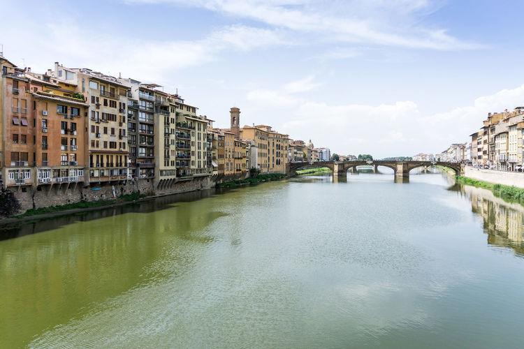 Ponte Santa Trinita Over Arno River Amidst Buildings Against Sky