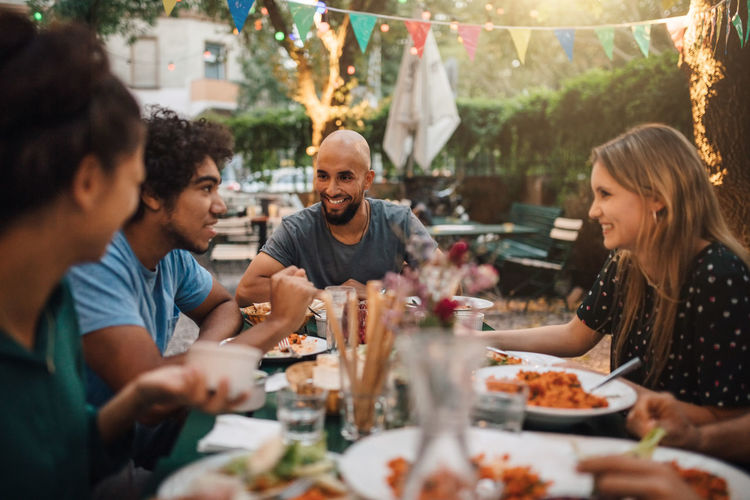 Smiling young man and women listening to male friend talking during dinner party in backyard