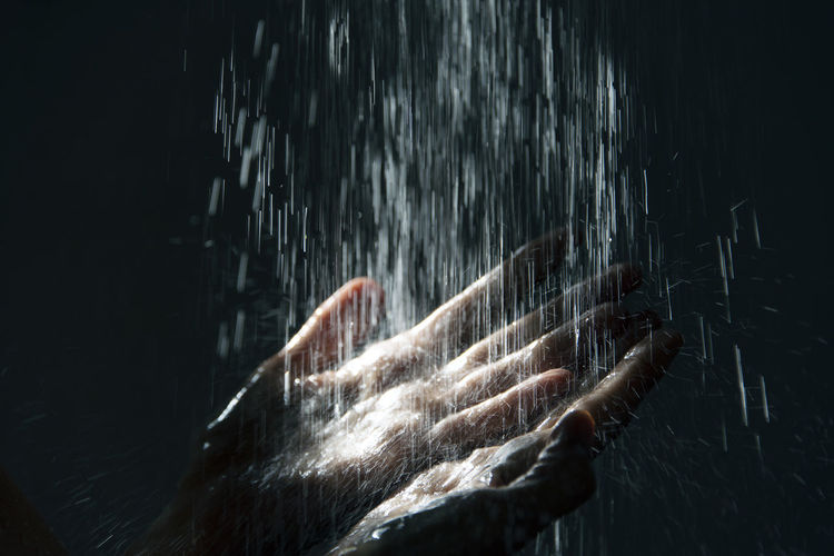 Close-Up Of Water Falling On Hands