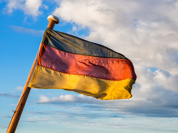 Low Angle View Of German Flag Waving Against Cloudy Sky