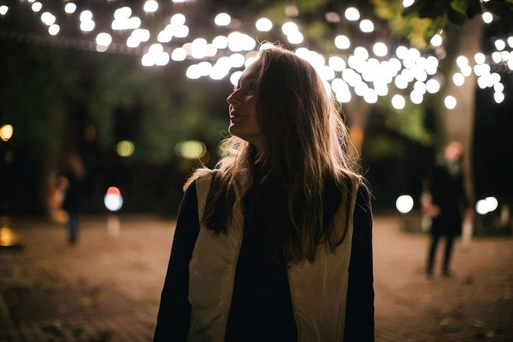 Woman looking away while standing against illuminated lights at night