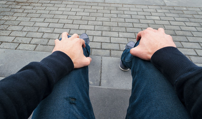 young man hold his knees and is nervously Fear POV Sitting Steps Waiting Adult Anxiety  Break Close-up Communication First Person View Human Body Part Human Hand Human Leg Jeans Lifestyles Low Section Men Nervously Only Men Outdoors Personal Perspective Real People Shock Standing