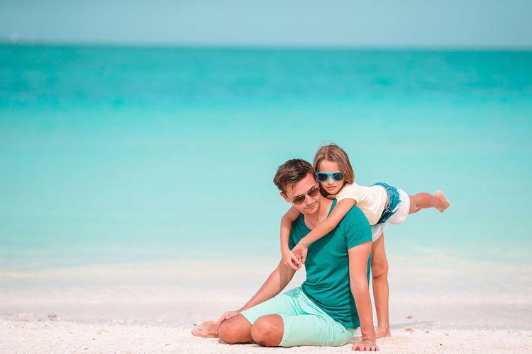 Man wearing sunglasses on beach against sky