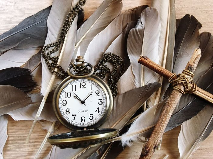 Close-up of clock with feathers on table
