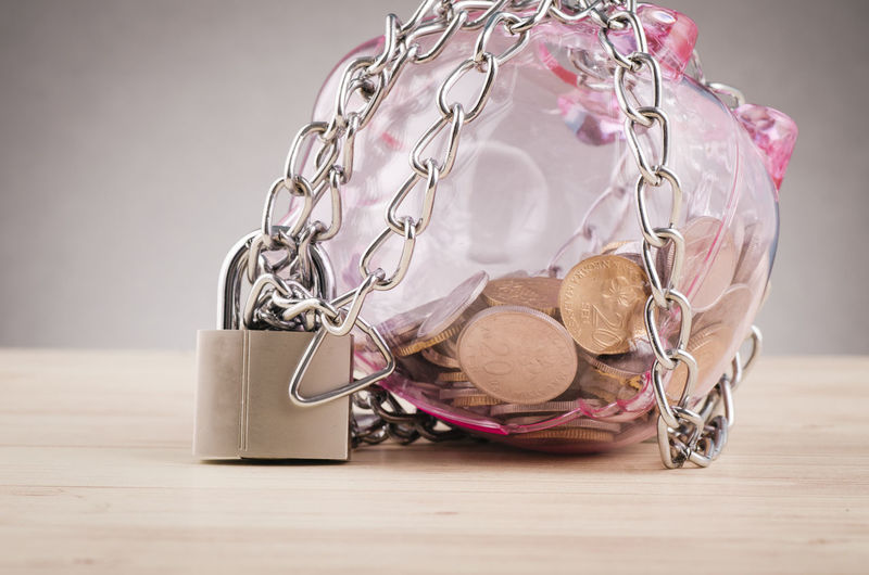 piggy bank surrounded by chains and padlock on wooden desk Table Still Life Indoors  No People Close-up Finance Bag Savings Connection Focus On Foreground Wood - Material Metal Glass - Material Security Technology Key Tied Up Investment Selective Focus Communication Personal Accessory