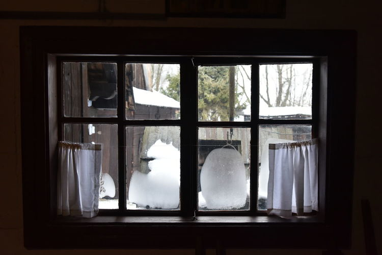 Close-up of glass window on snow covered house